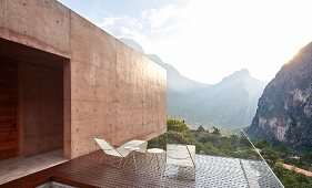 Sun shining behind mountains seen from balcony of architect-designed house