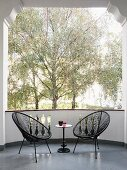 Zwei schwarze Acapulco-Chairs mit Beistelltischchen auf Balkon und Blick auf Bäume