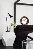 Weißer Designer-Nachttisch mit Retroleuchte neben schwarzem Bett