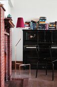 Brick fireplace, black piano and standard lamp in music room