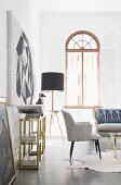 Standard lamp and open arched window in elegant lounge area