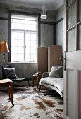 Blick in Zimmer mit Marmorverkleidung, Sprossenfenster und Tierfellteppich
