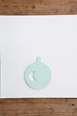 Christmas-tree bauble cut out of pale blue paper on white surface