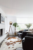 Black leather armchair, studio lamp and cowhide rug in front of fireplace