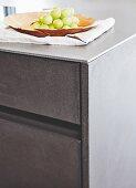 Küchenunterschrank mit Schubladenfronten in Betonoptik und Arbeitsplatte aus Stahl