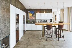 A spacious kitchen with white glossy cupboards and a stone-coated wall with a wooden table in the middle