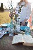 Frau steht hinter romantisch gedecktem Tisch mit offenem Buch