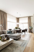 Elegant, open-plan living room in sandy shades with large windows
