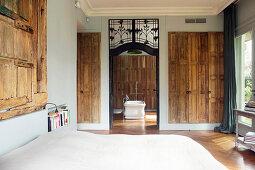 Old wooden doors on walls in bedroom with view into bathroom