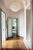 Spherical lamp in oval hallway with herringbone parquet floor in period building