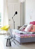 Tagesliege mit Matratzen und Kissen davor Beistelltischchen mit Keramikkrug, Bechern und Glasglocke