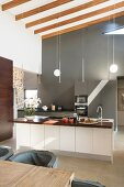 Elegant fitted kitchen with grey back wall and island counter in high-ceilinged room