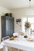 Table festively set in white in front of grey locker