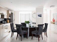 Elegant velvet-covered chairs around designer table in bright kitchen