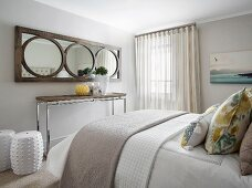Mirror with wooden frame above console table and white ceramic drum stool at foot of double bed in bedroom