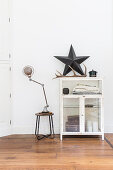 Star and antler on top of old glass-fronted cabinet