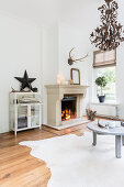 Lit fire and cowhide rug in living room