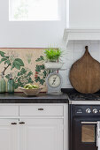 Old kitchen scales in front of botanical illustration in country-house kitchen