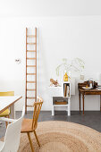 Ladder leaning against wall in dining room with high ceiling and white walls
