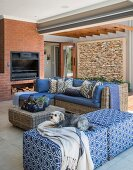Wicker furniture and open fireplace in brick wall in comfortable lounge area