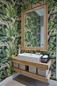 Floating oak washstand below mirror mounted on floral wallpaper in corner of bathroom