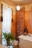 Hohes Schubladenschränkchen aus Holz im zweifarbig gestrichenen Bad