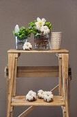 Blumensträußchen in Vasen und Baumwolle auf einer Leiter