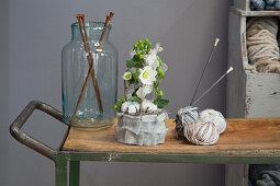 Winterliches Ikebana mit Christrosen in einer Manschette aus Filz