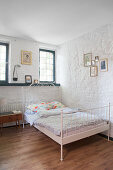 Metal bed in bedroom with whitewashed stone walls and lattice windows