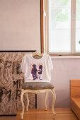T-Shirt über der Lehne eines alten Barockstuhls vor dem Fenster