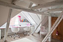 Desk below window in attic room with white roof beams