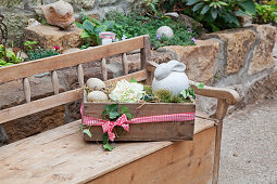 Holzkiste mit Osterdeko auf einer Holzbank, im Garten
