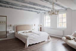 Large, white bedroom with simple furnishings