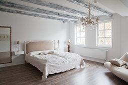 Großes Schlafzimmer in Weiß mit schlichter Einrichtung