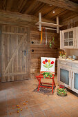 Loose cover embroidered with tulips on red chair in country-house kitchen