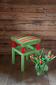 Crocheted seat cover on red and green stool against wooden wall