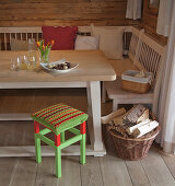 Crocheted seat cover on red and green stool next to dining table