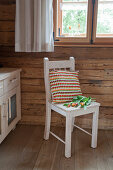 Crocheted cushion with floral motif on wooden chair