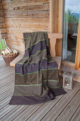 Brown blanket made from strips of various fabrics with decorative green seams