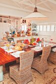 Wicker chairs around set dining table in open-plan country-house kitchen