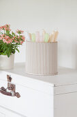 Pastel candles in container made from corrugated cardboard