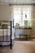 Metal bed next to window in bedroom with vintage-style wallpaper