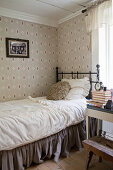 Metal bed with valance in bedroom with vintage-style wallpaper