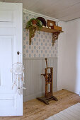Old wooden tool below shelf on wall with wainscoting and patterned wallpaper