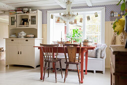 Red table with chairs and bench in Scandinavian country-house kitchen