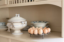 Egg rack, soup tureen and old crockery on kitchen dresser