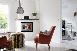 Red velvet armchairs in front of corner fireplace in white living room