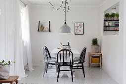 Black and grey spoke-back chairs around table in white dining room