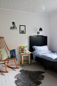 Rocking chair and black bed in child's bedroom