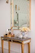 Mirrored table below mirror in Venetian style on bedroom wall
